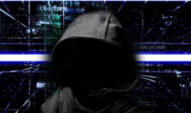 Person with face obscured shown from the chest up wearing a hoodie while vertical and horizontal lines and computer code glow in the background