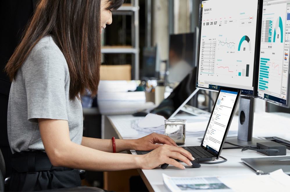 A woman works on her Surface Laptop 3 at her desk