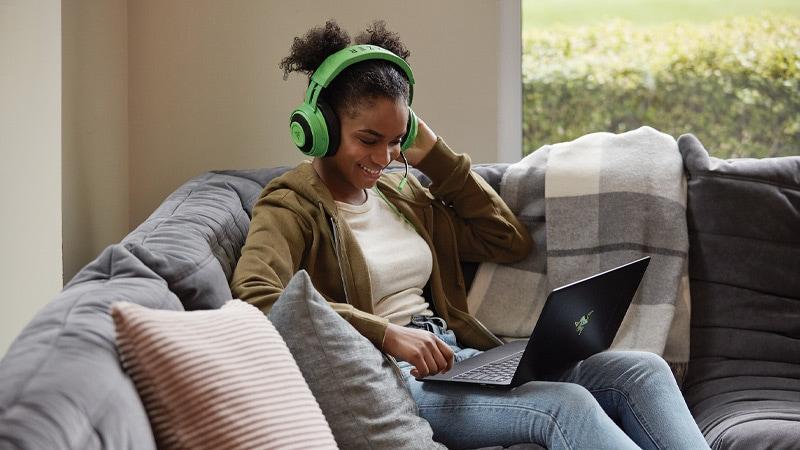 Kulaklýk takan genç bir kadýn kanepede uzanýrken, Windows 10 bilgisayarýnda bir oyun oynuyor.