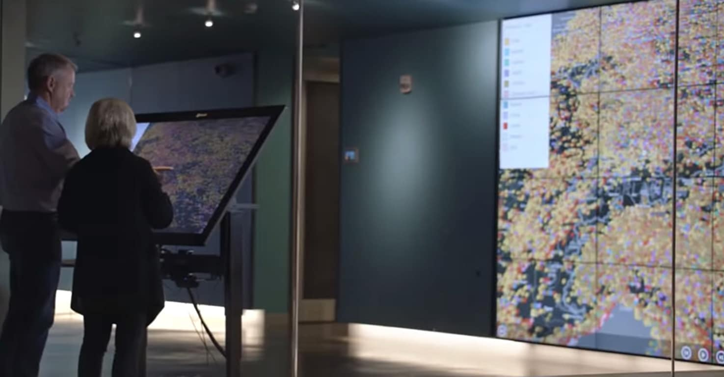 Photograph of two people standing in front of a large screen discussing what they see on the map displayed on the screen.