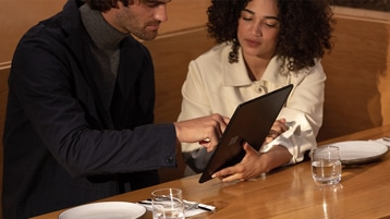 Two people work together on a new Surface Pro X for Business.