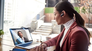 A person in business attire, wearing a wireless in-ear speaker, sits at a desk and appears to be participating in a video chat with someone who appears on her laptop screen.