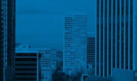 Blue-tinted photograph of skyscrapers and other buildings.