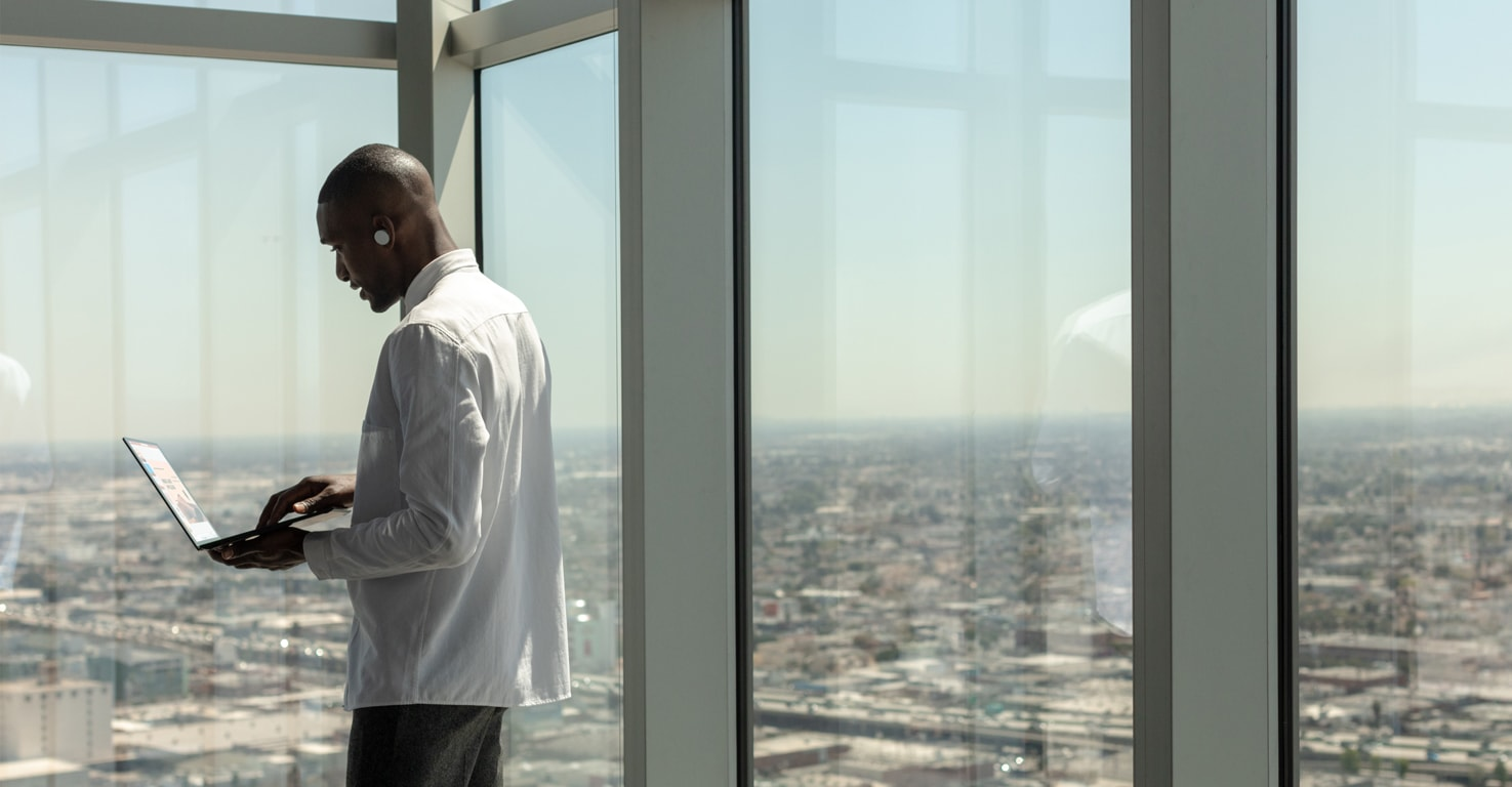 Photograph of a person holding a laptop and wearing an earpiece, standing by floor-to-ceiling glass windows overlooking a city below.