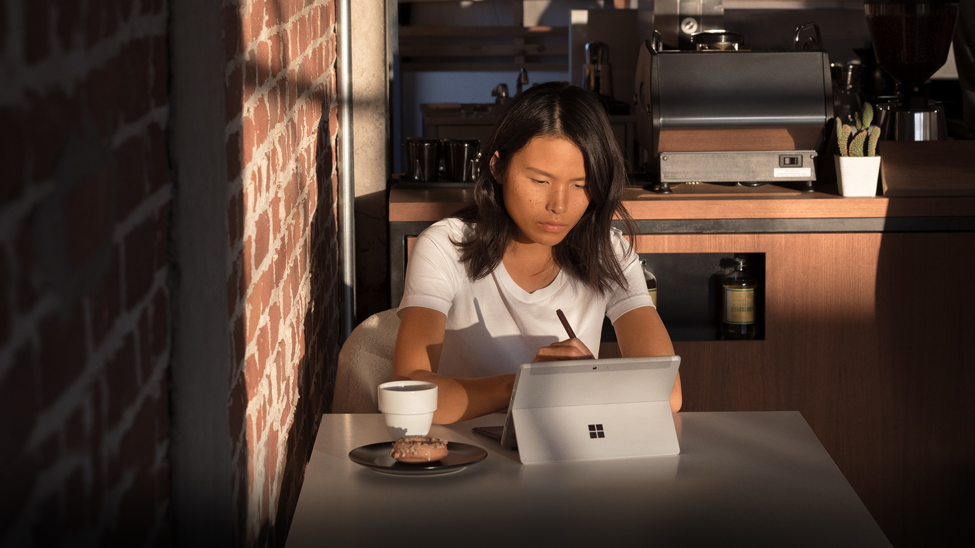 Young woman working on a Surface Go in a coffee shop