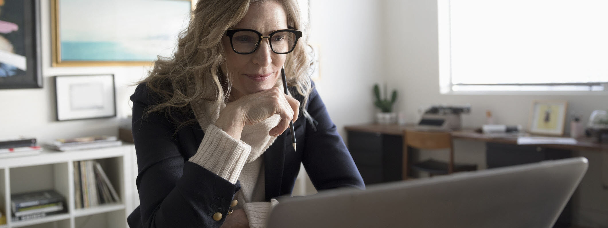 A woman in an office staring intently at her laptop on the desk in front of her.