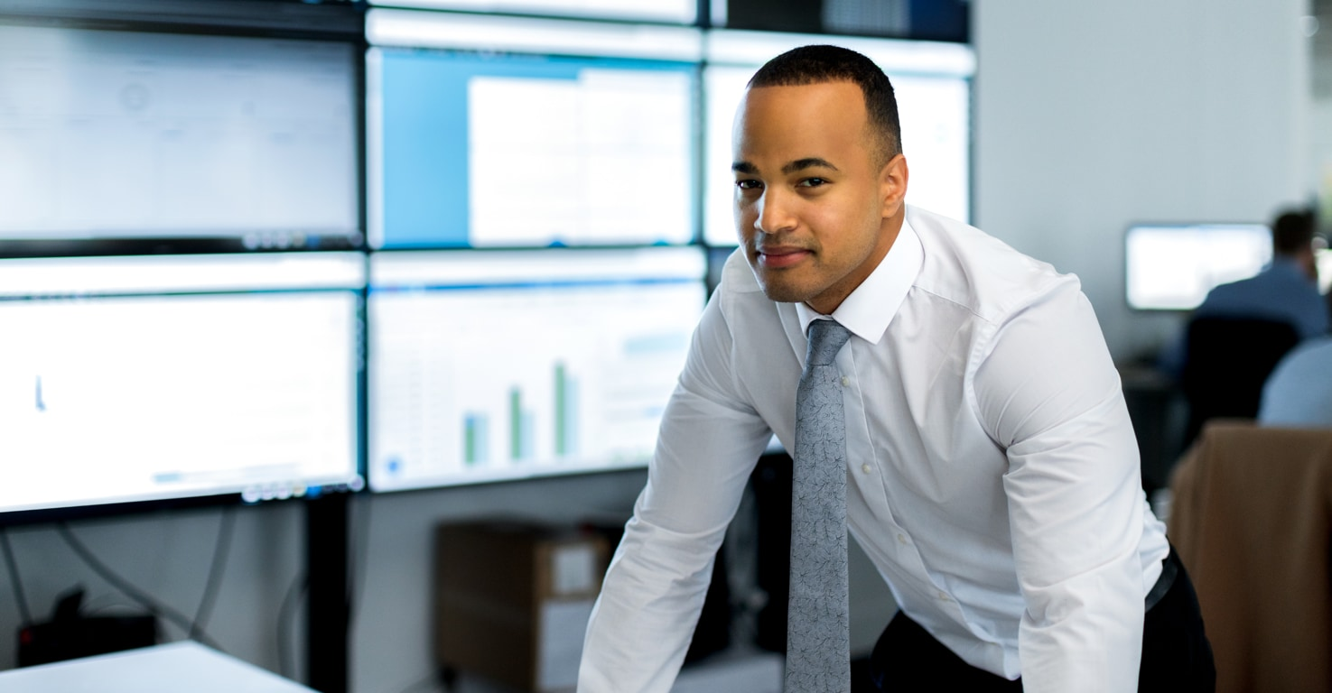 Photograph of a well-dressed finance person leaning on a desk in a financial services office. In the background is a wall of large monitors displaying information.
