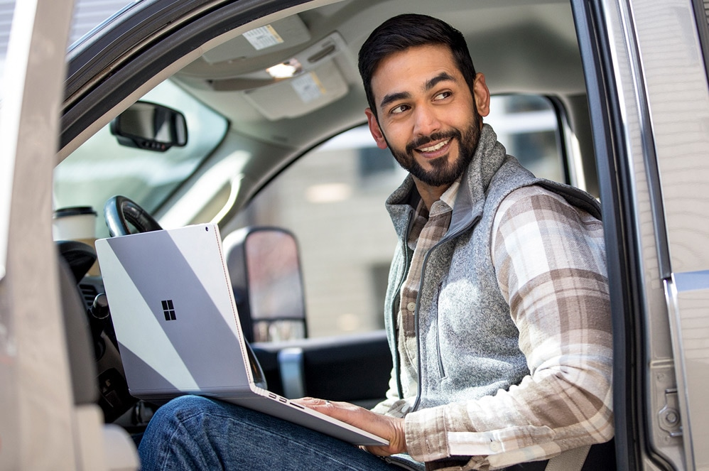A man uses Surface Book 2 on his lap from the driver's seat of a car