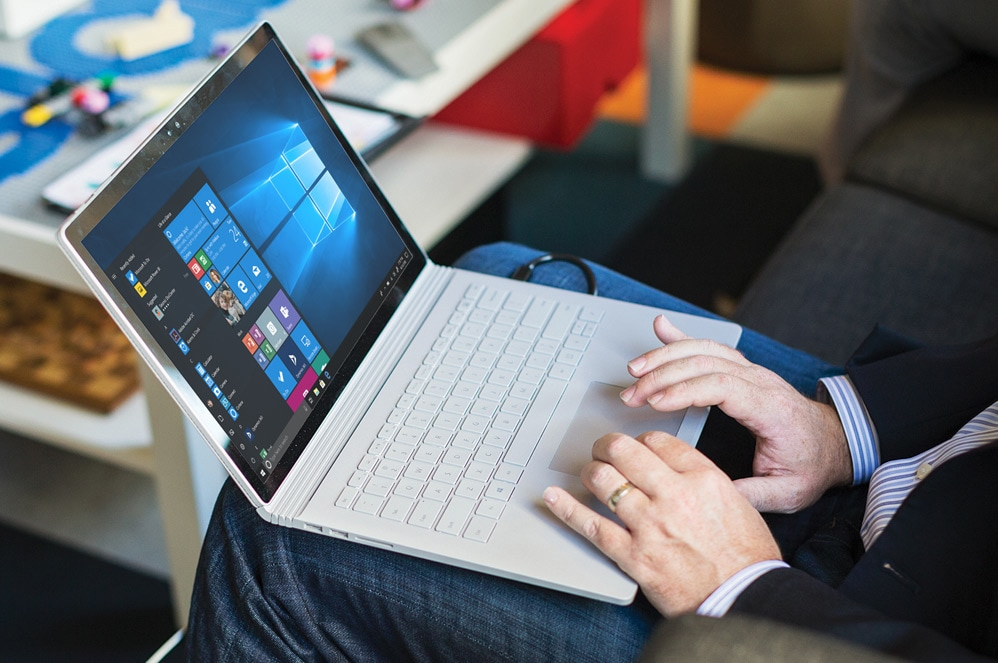 A person uses Surface Book 2 In Laptop Mode on their lap. The display shows the Windows Start screen