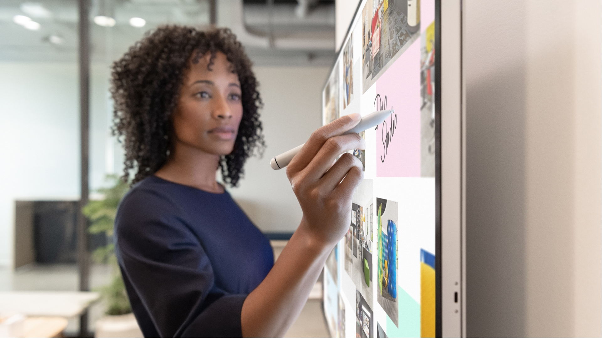 Woman using Surface Hub 2 Pen one Surface Hub 2S hanging on wall