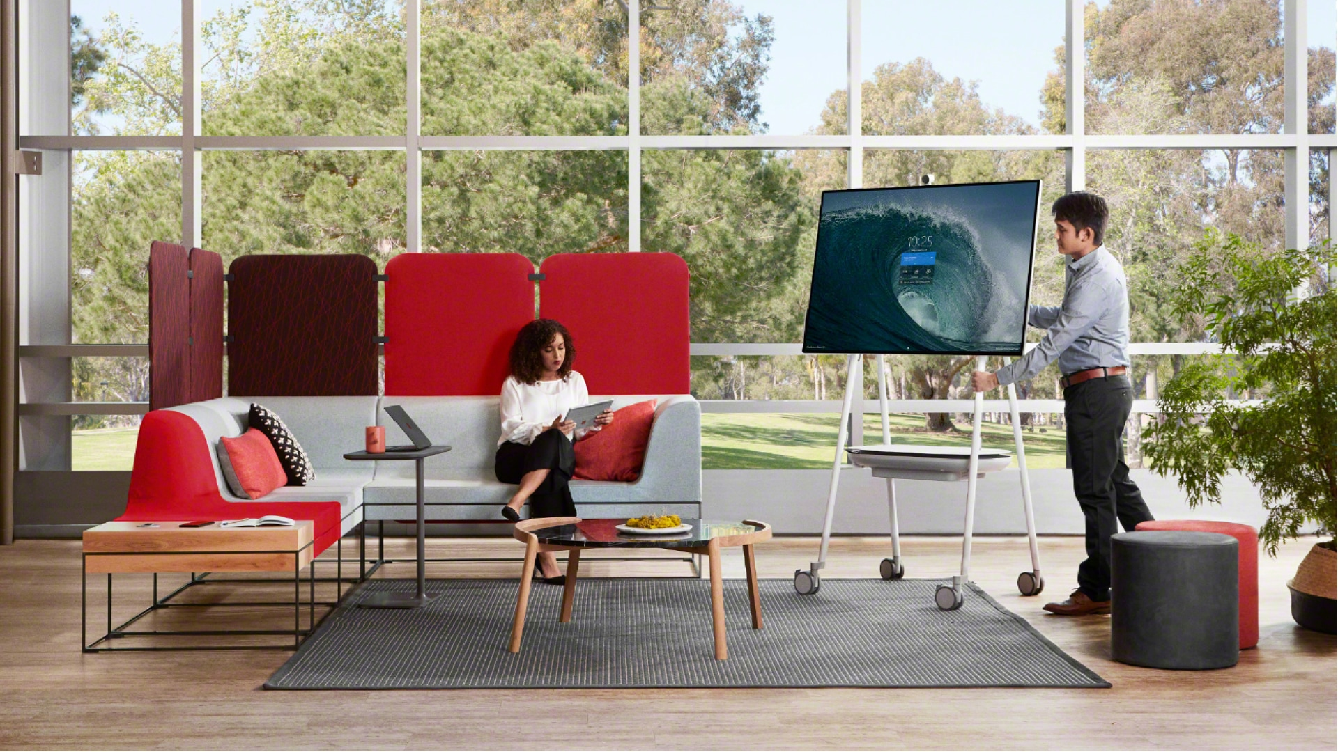 Man standing next to Surface Hub 2S while woman sits looking towards him on a couch