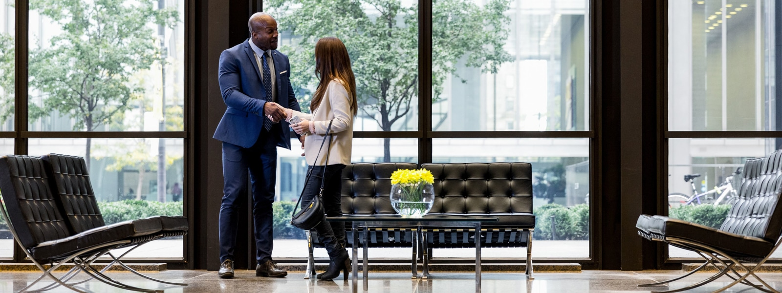 Businessman shaking hands with client in professional building lobby