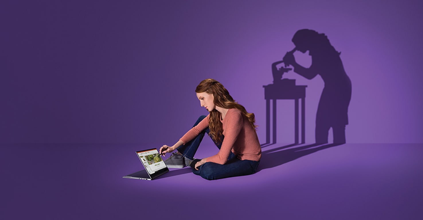 Photograph of a person seated on the floor using a stylus with a Surface Book 2 in Display Mode. The shadow formed in the background is the same person standing and looking into a microscope.