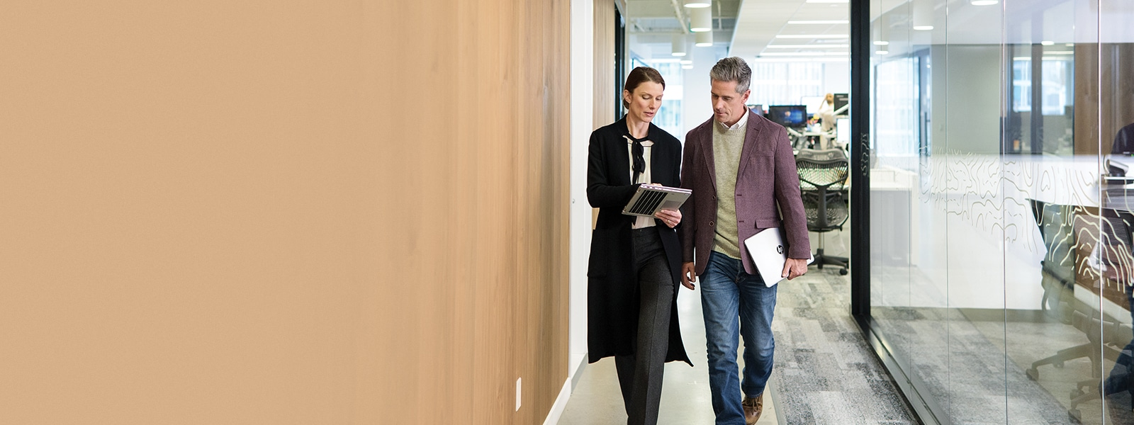 A man and woman walk in an office setting.