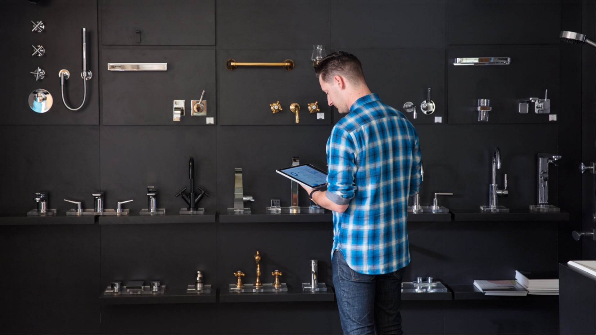 Man standing with tablet looking at wall of demo faucets
