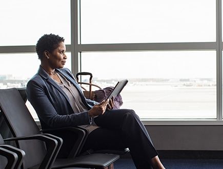 A person sitting in an airport holding a tablet and looking out the window.