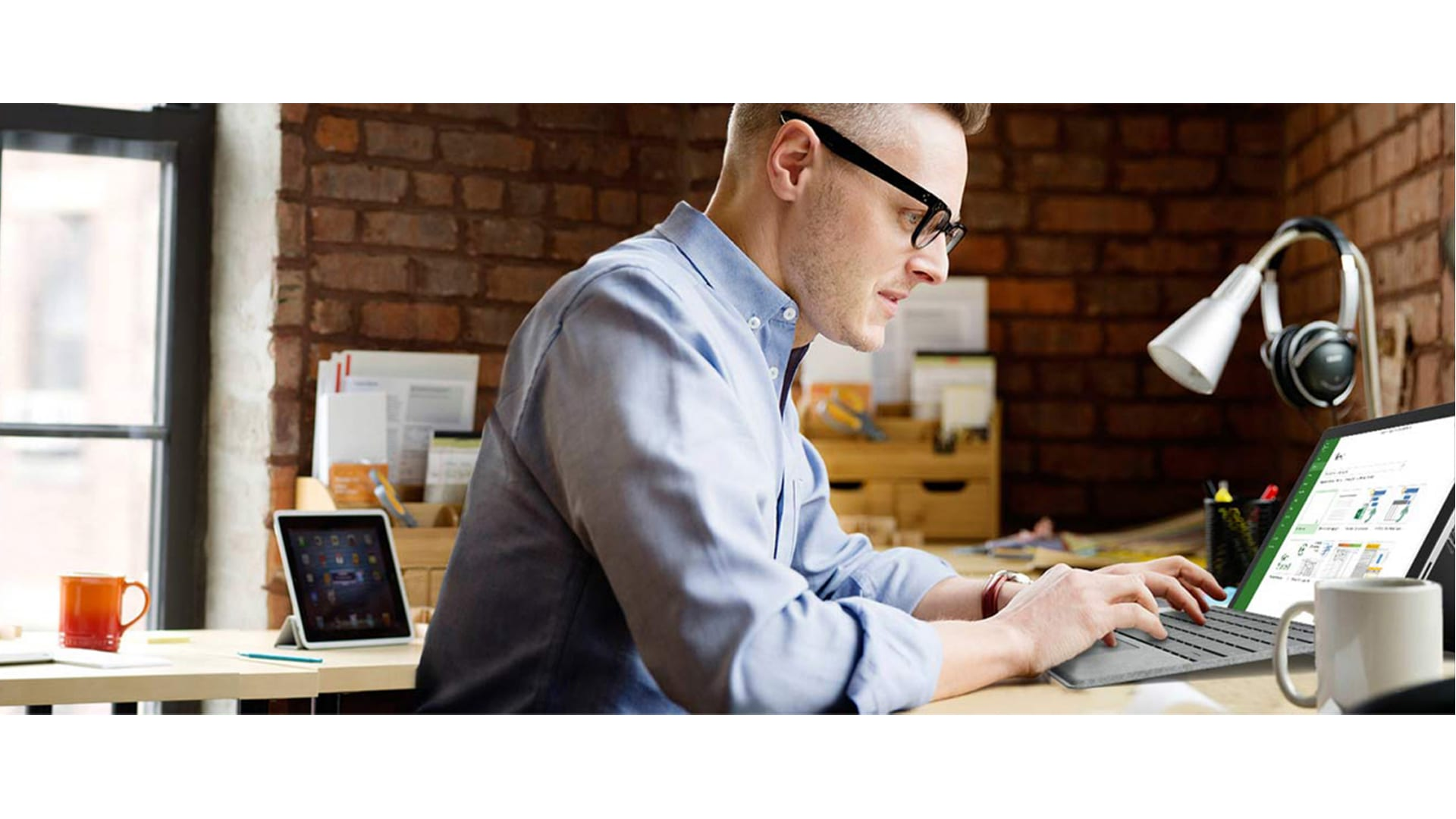 Man sitting at desk, working on laptop