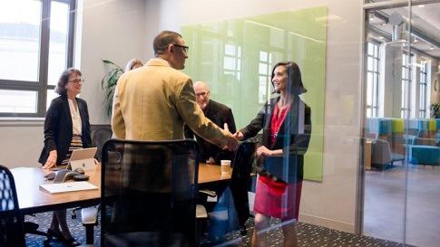 Mehrere Menschen befinden sich in einem Büro. Die zwei im Vordergrund geben sich lächelnd die Hand.