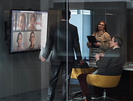 Three coworkers in a meeting room on a video call with additional participants.