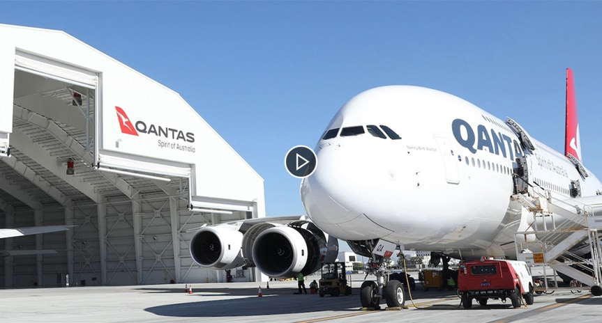 Still image from video showing the nose of a Qantas airplane outside of a hangar.