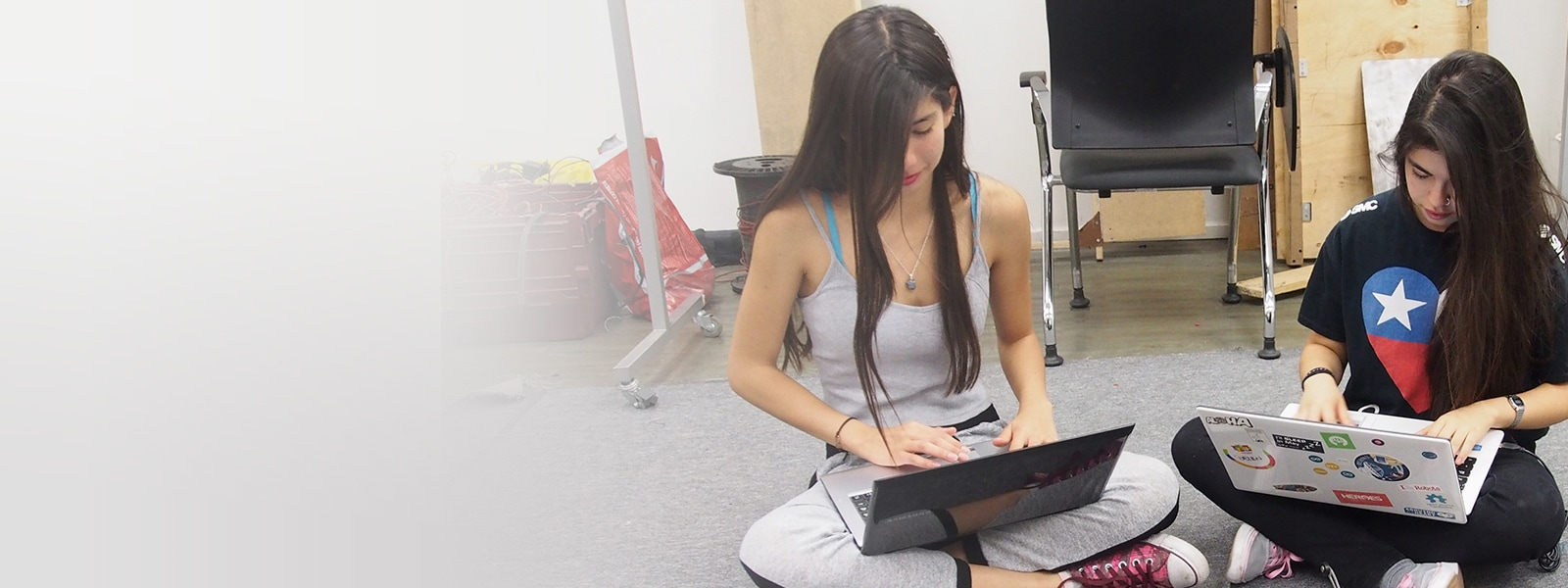 Two female students sitting cross-legged on the floor and working on laptops in a CS class