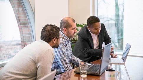 Drei Männer stehen an einem Hochtisch und arbeiten an zwei Laptops.
