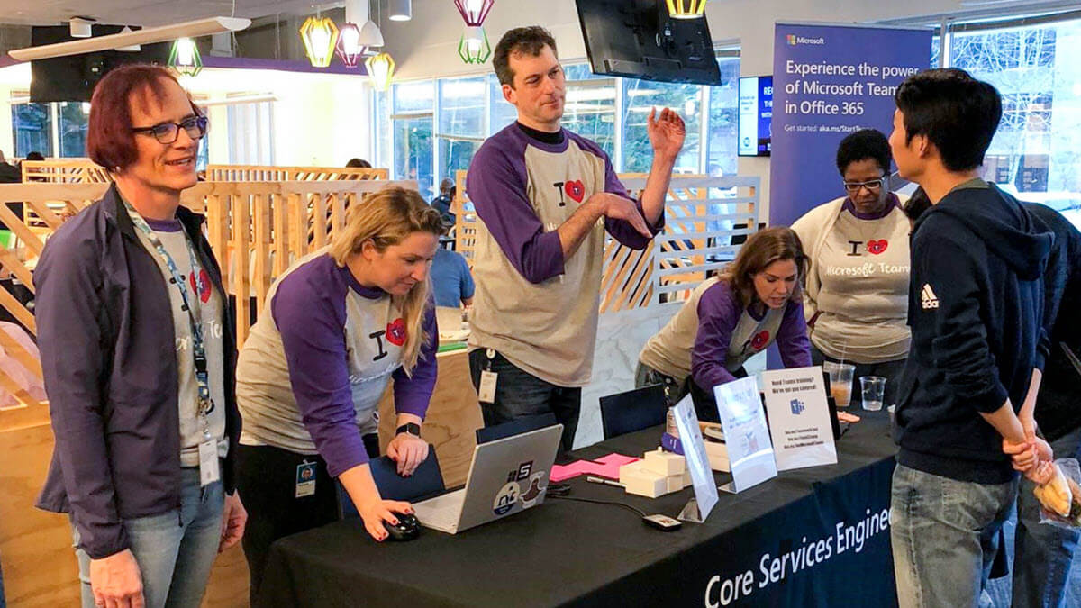 A photo illustrating a Teams Tuesday event. It shows members of the adoption team engaging with a Microsoft employee at a Teams Tuesday kiosk.