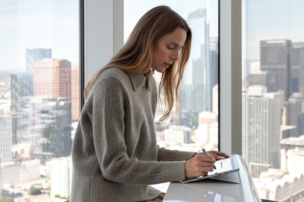 Frau macht Notizen mit ihrem Surface Pro 7 for Business