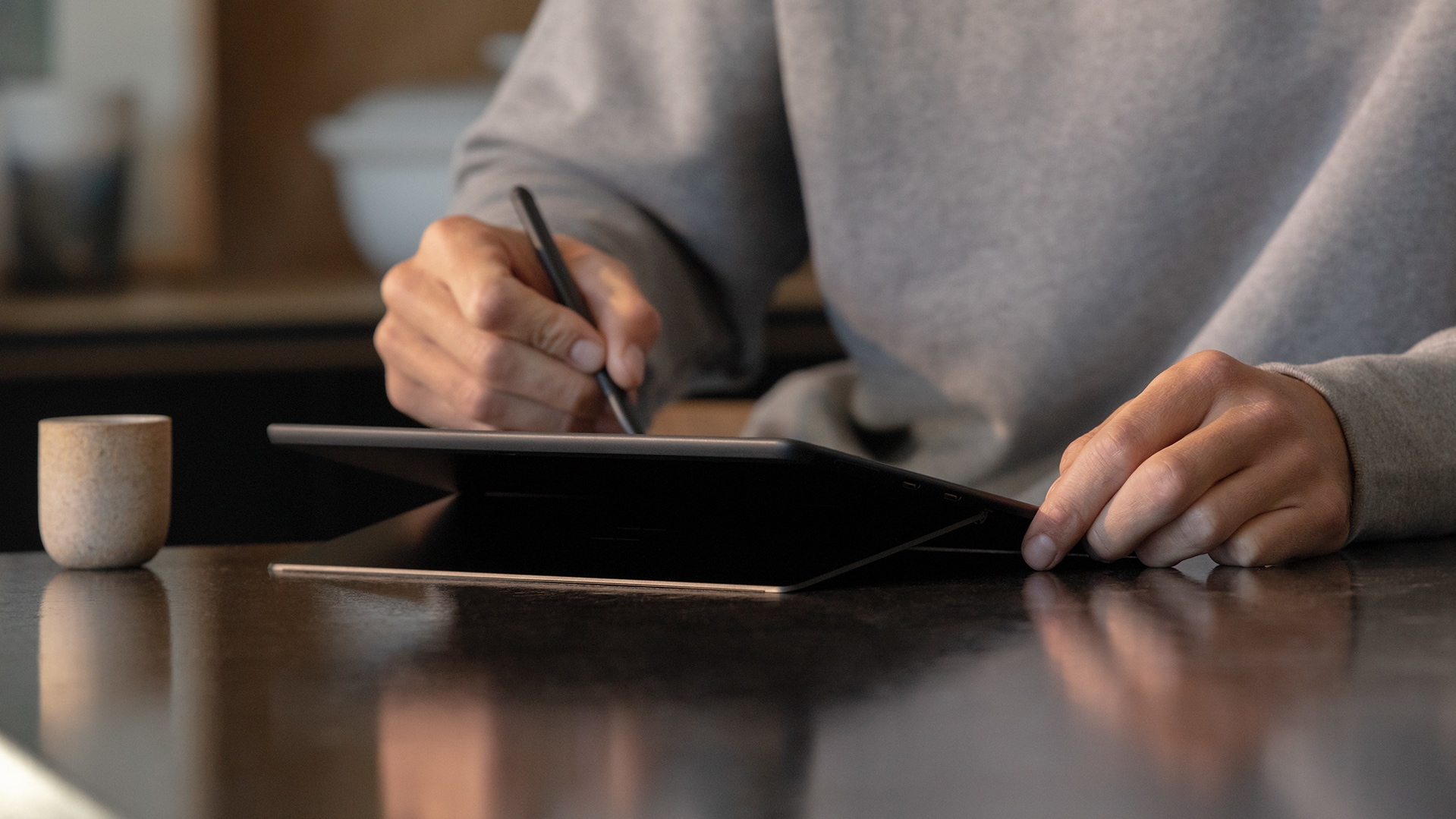 Woman sitting at table working on Surface Pro X