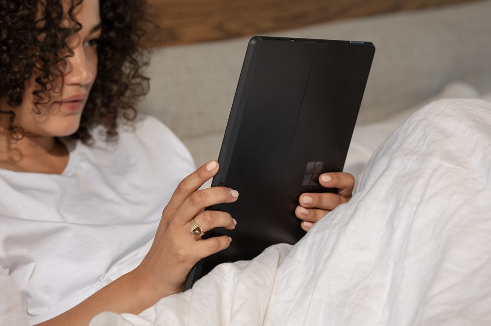 A woman holds Surface Pro X in tablet mode