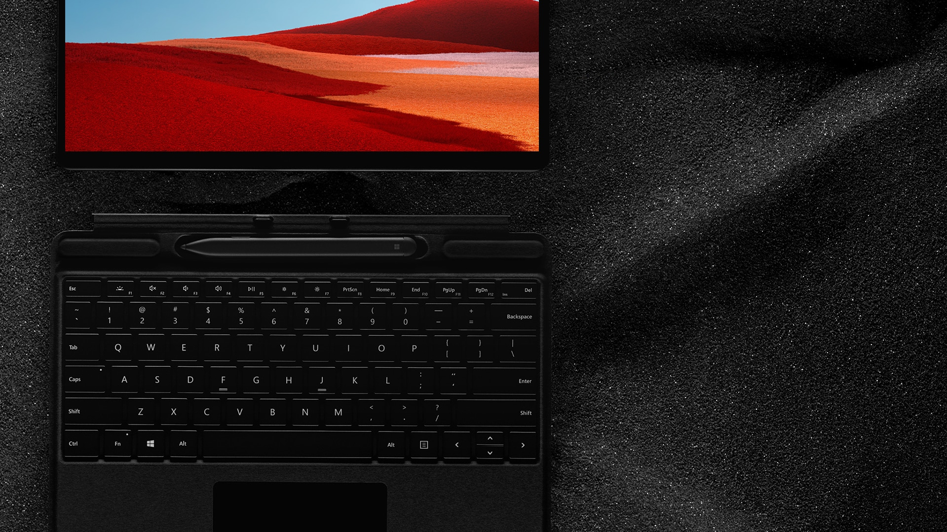 Surface Pro X met Surface Slim PenXXXXXX Slim Pen en Surface Pro X Signature keyboard die plat op zwart zand ligt