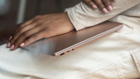 A woman has a closed Surface Laptop 3 on her lap