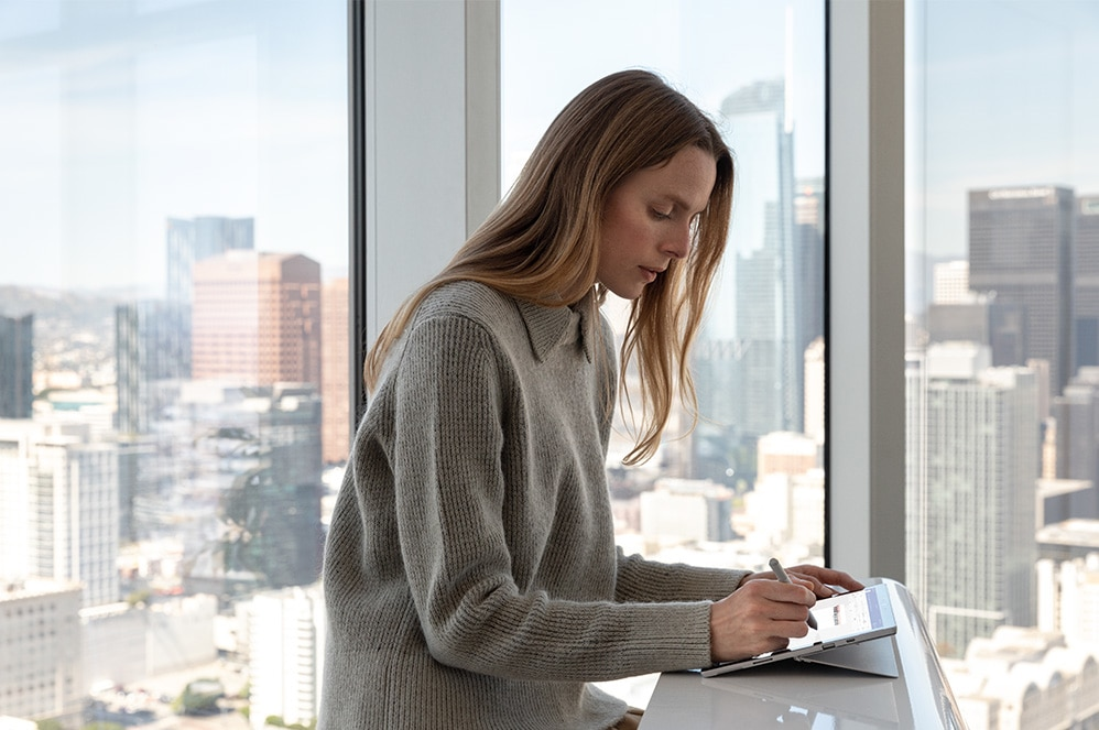 Woman using Surface pen on Surface device screen at a desk