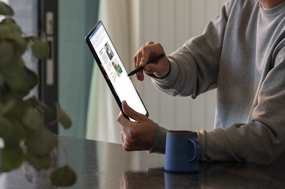 Person holding Surface Pro X looking at screen