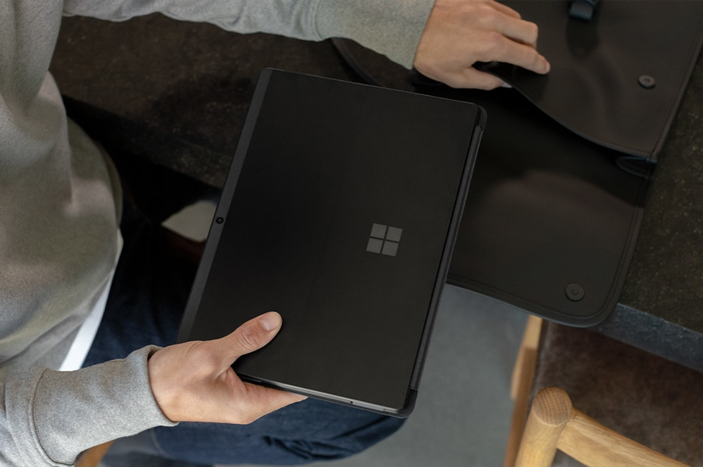 Person pulling Surface Pro X out of a bag