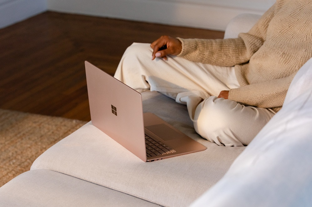 A woman sits in front of Surface Laptop 3 on a sofa