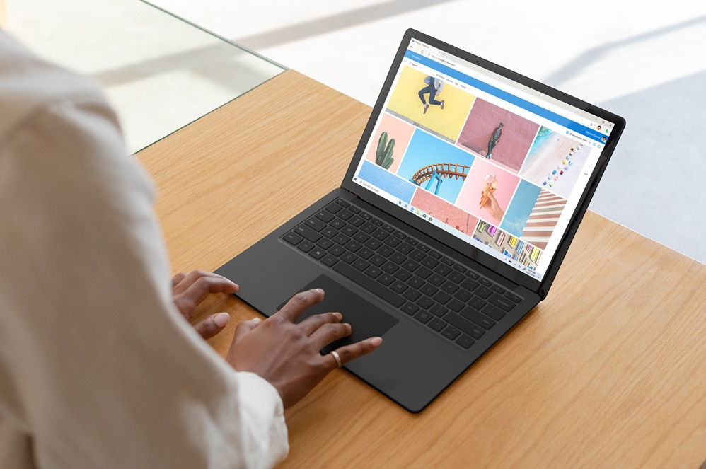 A woman types on the large keyboard  of Surface Laptop 3
