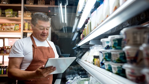 Grocery clerk looking at tablet