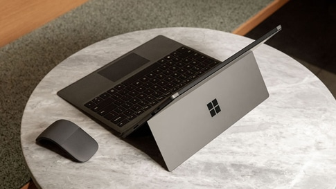 Surface Pro 7  in Matte Black with Surface Arc Mouse on a small table