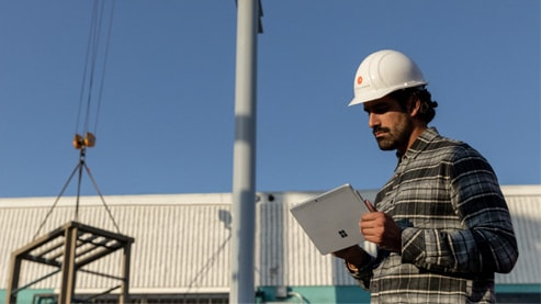 Person on a job site holding a Surface device