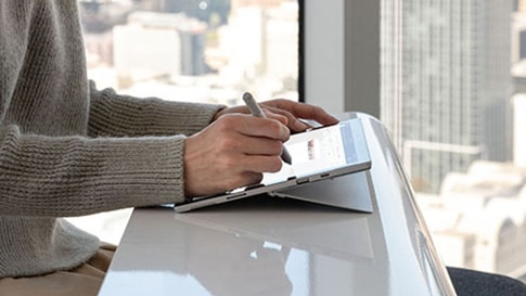 A woman writes on Surface Pro 7 with a Surface Pen