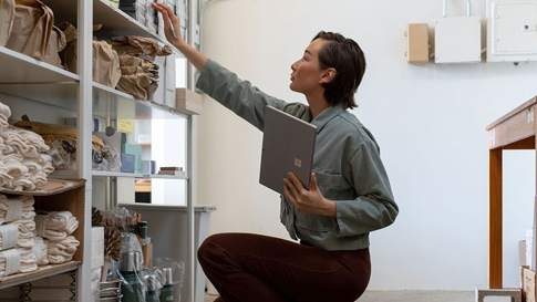 A woman holds Surface Pro 7  while reaching up to a bookshelf