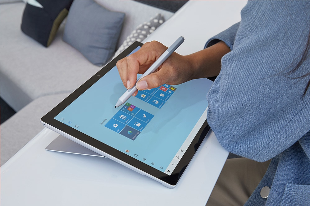 A woman touches the screen of her Surface Pro 7