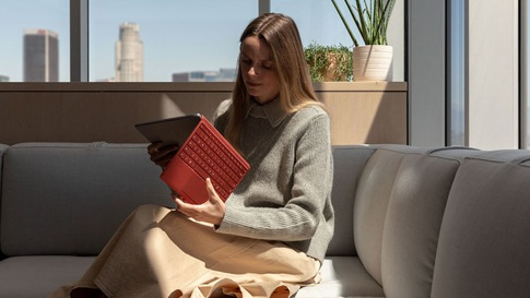 A woman sits on a sofa opening Surface Pro 7 with a Poppy Red Type Cover