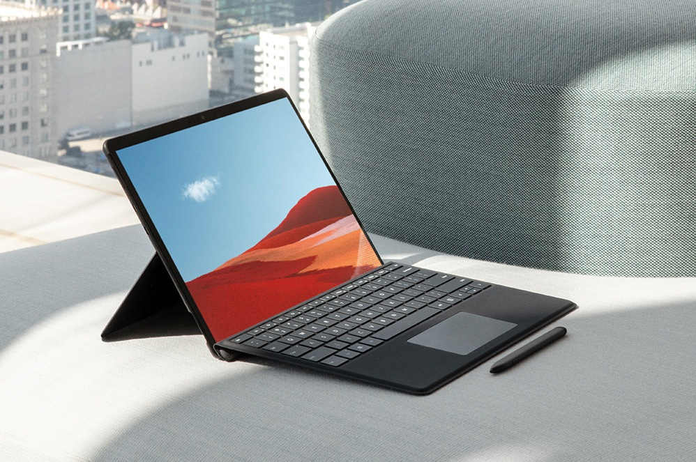 Surface Pro X showing display, keyboard, and pen on table