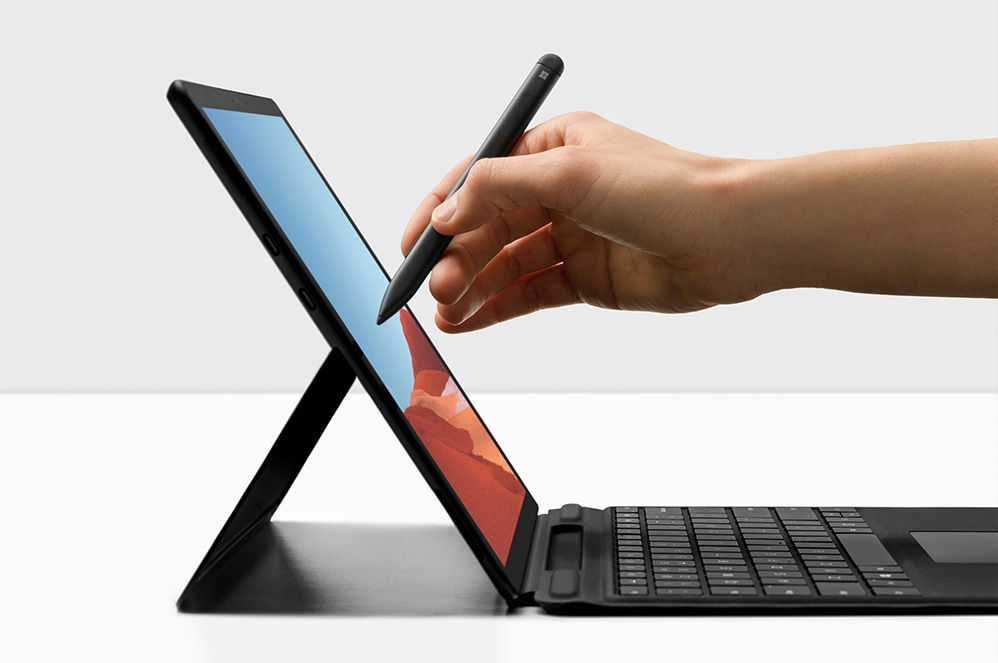 Close-up of hand holding Surface Slim Pen using it on Surface Pro X display, keyboard showing
