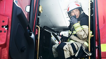 A firefighter in the fire engine, talking over the radio.