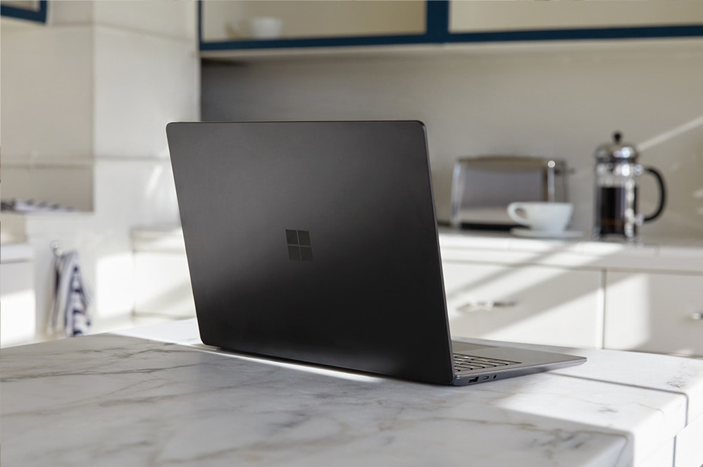 A woman holds Surface Laptop 3 in her hand while reaching for an item on a shelf