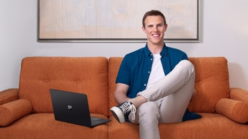 """Mackenzie """"Mac"""" Book on a couch with a Surface Laptop 2."""