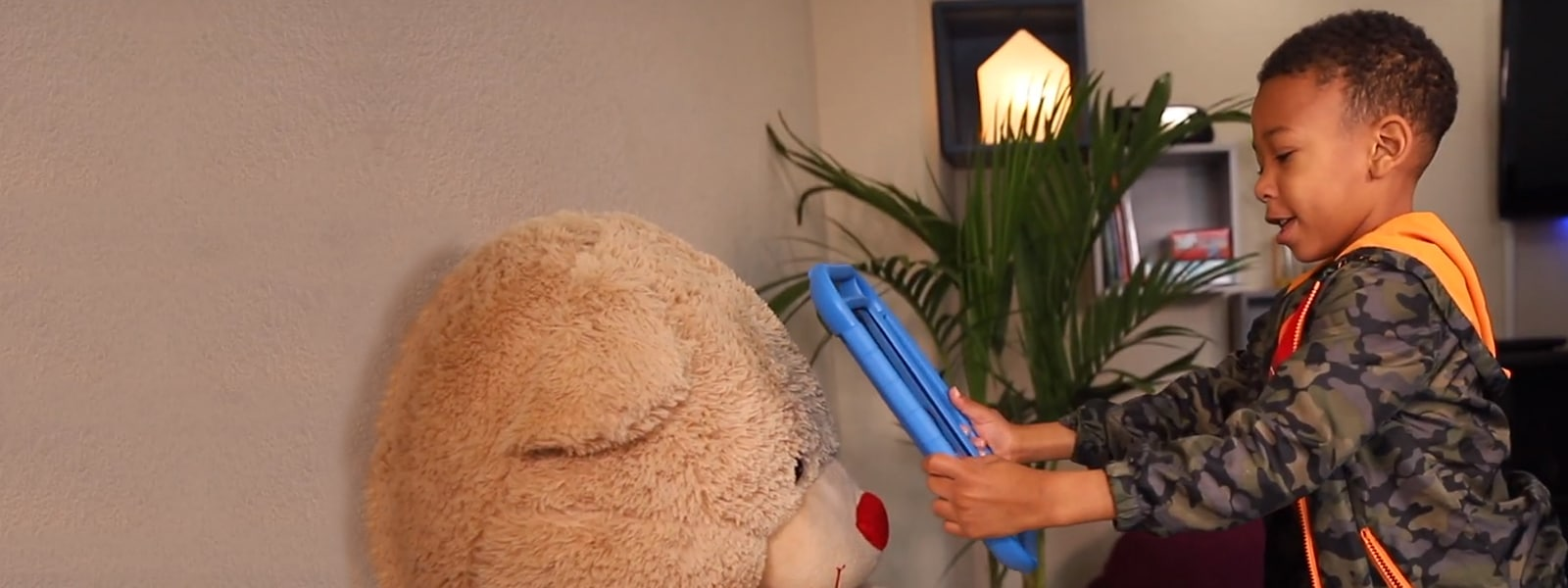 Young boy uses a tablet with InnerVoice app to interact with toy.